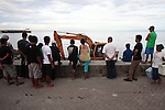 People watch a backhoe at work along the seaside promenade in the town of Dumaguete, Negros island, Philippines. June 16, 2011.