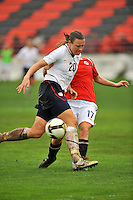 Abby Wambach fends off a clinging Norwegian defender. The USA defeated Norway 2-1 at Olhao Stadium on February 26, 2010 at the Algarve Cup.