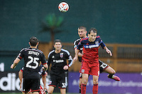 Washington, D.C.- March 29, 2014. Mike Magee of the Chicago Fire heads the ball against Perry Kitchen (23) of D.C. United.  The Chicago Fire tied D.C. United 2-2 during a Major League Soccer Match for the 2014 season at RFK Stadium.