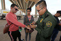 El Paso, Tx - NEWS:   Ride along with Customs and Border Protection agents, El Paso, Tx, Monday, April 29, 2019.<br /> <br /> <br /> PICTURED:  Cubans Yudier Angel Guerrero, 29, and his girlfriend Lina Telles, 20, are part of a group of 18 migrants - including 2 children and a a teenager - seeking asylum in the USA.  The group of migrants turned themselves in to border patrol agents near the border fence.<br /> Customs and Border Protection agent Edward Butron, 35, places an orange wrist band on Guerrero's wrist.<br /> This area is called 'Nicholson's Crossing' by border patrol agents.  <br /> <br /> <br /> (Angel Chevrestt, 646.314.3206)