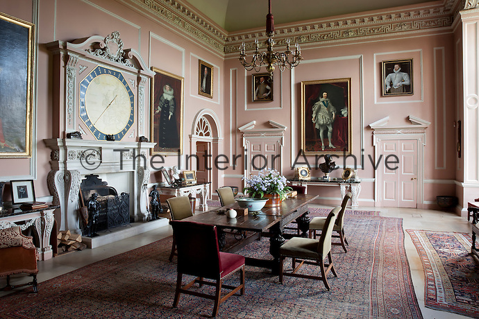 The dining room decorated in the Palladian style, with pedimented doorways and an eye catching clock above the mantelpiece.16th century Fitzwilliam portraits hang from the pink and white walls