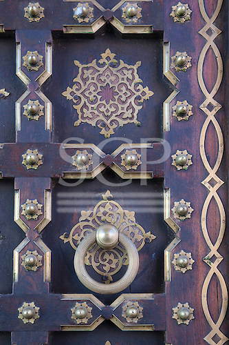 Jaipur, India. Panelled door with brass studs and decorations, and a large ring handle; City Palace