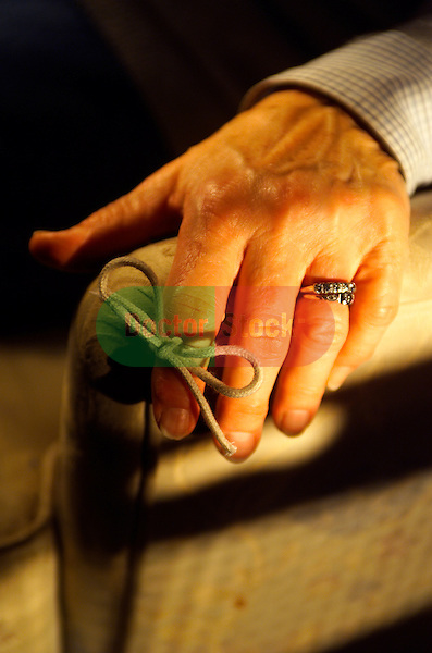 close-up of hand of elderly woman with string tied on index finger resting on chair arm