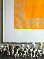 This bright orange artwork hangs above a collection of sheep ornaments.