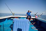 A fisherman scans the water looking for Blue Fin Tuna. Gulf of St. Lawrence near North Rustico, Prince Edward Island, Canada.