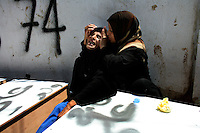 Tyr, Lebanon, July 21 2006.A relative comforts Mariama Abdallah, 50, who lost 12 persons from her family in the Israeli bombing of a minibus in Marwaheen, including her husband, several of her children and grandchildren. More than 80 Israeli bombardment victims' bodies have been kept in refrigerated trucks for several days by the Lebanese authorities to allow for identifications before being put in coffins labeled with their names and details to be buried in a mass grave nearby.