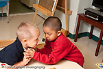 Education preschool 3 year olds two boys struggle over possession of toy or puzzle piece conflict horizontal
