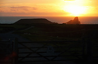 The sun sets over Worms Head in Rhossili, Gower, Wales, UK.