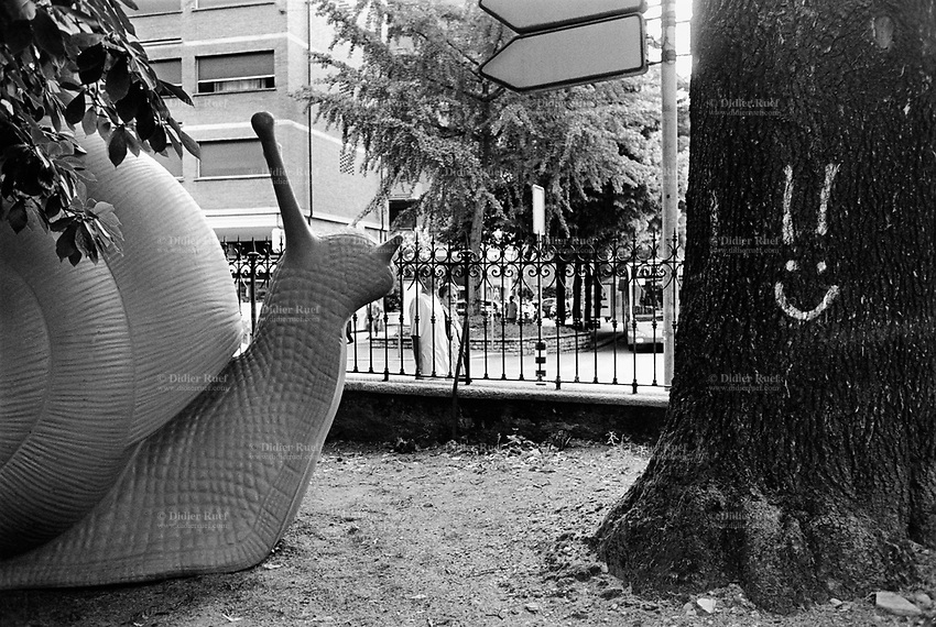 """www.didierruef.comSwitzerland. Canton Ticino. Lugano. REgeneration by Cracking Art Group is a project curated by Must Gallery. A snail, a couple, a public bus and a graffiti of a smiling face on a tree's trunk. A huge snail with a height of 2.30 meters is wandering in a park. The Cracking Art Group plays with the city in order to rebuild it ideally and mentally and break with the daily routine rediscovering both the urban crossing and landscape. The Cracking Art Group chose the snail because it conveys three different metaphors through contemporary art language: the first one is connected to hearing, since the snail's spiral reminds of the human ear; the second one can be related to living, given that the snail carries its home on its back: the third considering that the snail is made of recyclable plastic. The Cracking Art Group' project """"REgeneration"""" embodies another important value, sustainability. This means leaving a mark - an artistic mark - on the metropolitan landscape with an ethically responsible approach to ambient. 12.08.13 © 2013 Didier Ruef"""