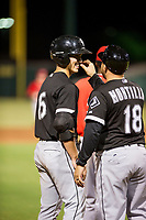AZL White Sox third base coach twists the mustache of JJ Muno (15) after hitting a triple against the AZL Angels on August 14, 2017 at Diablo Stadium in Tempe, Arizona. AZL Angels defeated the AZL White Sox 3-2. (Zachary Lucy/Four Seam Images)