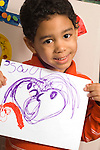 Preschool classroom New York City proud boy holding up drawing of human figure made with marker vertical Hispanic American