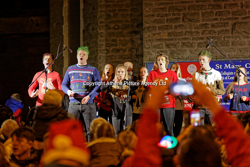 """Pictured: Youngsters sing outside St Mary's Church during the Christmas parade in Swansea, Wales, UK. Sunday 19 November 2018<br /> Re: Swansea Christmas parade attended by thousands has been branded a """"shambles"""" for having just three floats.<br /> The annual festive event in south Wales, which took place on Sunday, promised """"dynamic dance-troupes"""" as well as """"spectacular shows and stages"""".<br /> But the parade was scaled down, leading to a barrage of criticism on social media because of roadworks in the city centre. <br /> The leader of Swansea Council, Rob Stewart apologised on Facebook and said the parade was not """"good enough"""".<br /> Parents took on social media to voice their anger, calling the event """"a load of rubbish"""" and claiming there was nothing for young children apart from """"a loud music float with Santa on""""."""