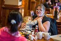 A mother comforts her daughter who is about two or three years old with a breastfeed while sitting at a table in the family restaurant and play area ofn a pub.<br /> Lancashire, England, UK<br /> <br /> Date Taken:<br /> 07-01-2015<br /> <br /> © Paul Carter / wdiip.co.uk