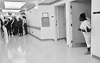 A hospital patient peers out her door to check out all the fuss in the hallway as several Miss USA delegates and their entourage make a PR stop at Methodist Hospital in Gary, Indiana.....