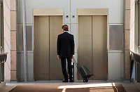 Businessman in suit waiting for lift/elevator in city environment.
