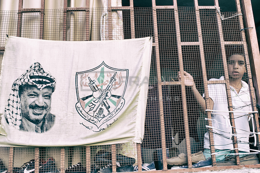 Kid in his house behind his window with the flag and the picture of Yasser Arafat the PLO leader as an eternal reminder for the Palestinian struggle. Shatila, Beirut. Lebanon. August 2015
