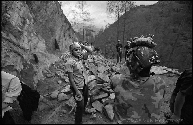 A Maoist rebel soldier of the People's Liberation Army rests after unloading rocks that she carried on her head during construction of the Martyr's road near the village of Nuwagaun in the Maoist controlled district of Rolpa on 24 June 2005. The Maoists required one person from each household in Rolpa and Rukum districts to contribute to the construction of the road for 10-15 days. The road built completely by hand labor is the first one to connect to the rural villagers in this area.<br />