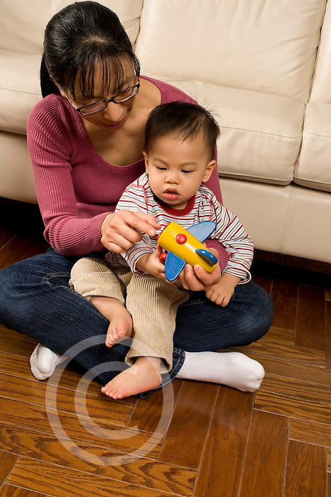 language development 16 month old toddler boy talked to by mother shown how propeller on toy airplane works Asian American Chinese vertical