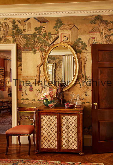 A gilt-framed, oval mirror hangs above an antique cabinet; the wall behind is hung with wallpaper with a Chinese scene motif.