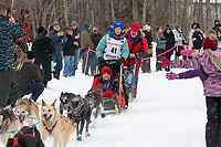 Jessica Klejka and team run past spectators on the bike/ski trail near University Lake with an Iditarider in the basket and a handler during the Anchorage, Alaska ceremonial start on Saturday, March 7 during the 2020 Iditarod race. Photo © 2020 by Ed Bennett/Bennett Images LLC