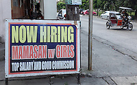 In borad daylight, a sign outside a 'girly bar' advertises job openings for prostitutes and their keeper, or 'mamasan', Angeles City, Republic of the Philippines, 08 November 2014. The 'sin city', which sprung up on the fringes of a US Air Force base during the Vietnam war, has a reputation for cheap sex, and was a favourite destination for alleged murderer Rurik Jutting, who used to fly to Angeles City from Hong Kong for debauched weekends. The British banker is currently on remand at a secure facility in Hong Kong for allegedly murdering two Indonesian prostitutes in his flat whilst high on alcohol and cocaine.