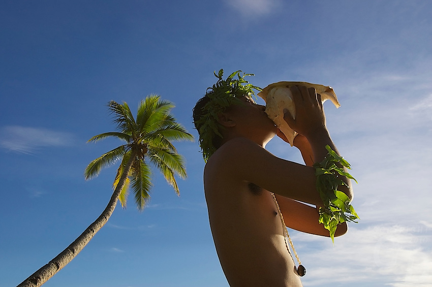Traditional Chuukese blowing into a shell as a welcome call on the island of Chuuk also know as Truk Lagoon in Micronrsia, South Pacific