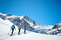 A group ski touring to the Turtmanntal Hut with the Turtmanngletscher ice fall in the background. Switzerland.