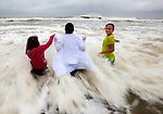 ST GEORGE ISLAND, FL- JUNE 6:  From left, Ryleigh Fisher, her sister Holly Fisher and cousin Hannah Helm, from Elizabethtown, KY play in the heavy rain and surf on St George Island, FL as tropical storm Andrea approaches the Florida panhandle. St George Island is located between Carrabelle, and Apalachicola, FL.  <br /> (CREDIT: Mark Wallheiser for Getty Images)<br /> ©2013 Mark Wallheiser