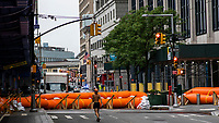 """NEW YORK, NY - AUGUST 4: People walk next to water barriers used to prevent flooding at the South Street Seaport as city gets ready for tropical storm Isaias on August 4, 2020 in New York City. The Tri-State area """"New York, New Jersey and Connecticut"""" is preparing for torrential rain, strong winds from Tropical storm Isaias. (Photo by Eduardo MunozAlvarez/VIEWpress)"""