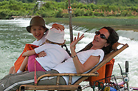 Family on a bamboo raft travelling down the Yulong River,  Yangshuo, Guangxi, China.