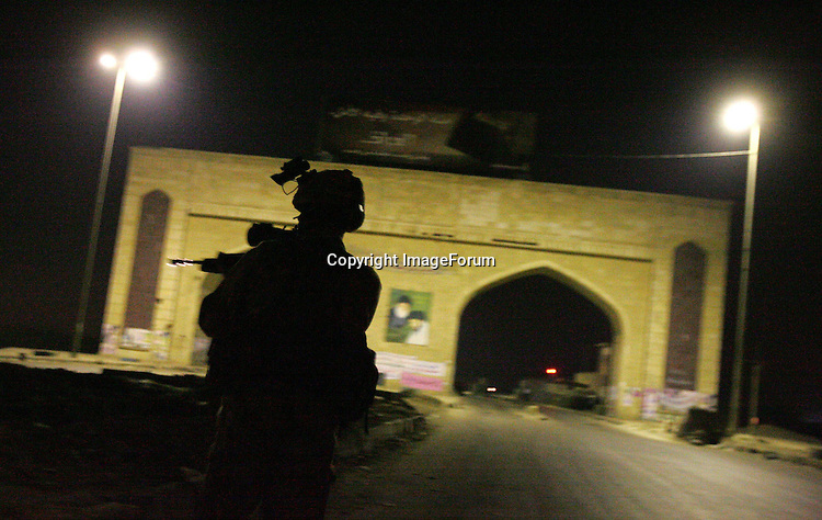 Members of the Royal Air Force Regiment 1 Squadron approach an Iraqi Police check-point at Basra Arches as they carry out a night patrol on the perimeter of Basra Airport Base in southern Iraq, in the early hours of 12 October 2005, ahead of the constitutional referendum on 15 October. The RAF Regiment is tasked with protecting airbases and other RAF assets around the world. AFP PHOTO / JOHN D MCHUGH