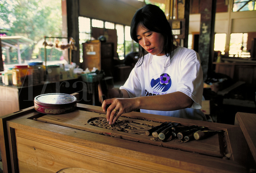 Young carver in a furniture shop with handtools. Chang Mai, Thailand. Chiang Mai, Thailand.