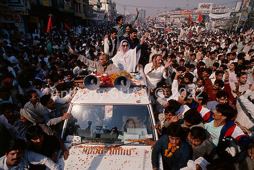 Gujranwala-Punjab, Pakistan<br /> November 12, 1988<br /> <br /> Benazir Bhutto arrives at a massive campaign rally in the Punjab province.<br /> <br /> Benazir Bhutto is the eldest child of former Pakistan President and Prime Minister Zulfikar Ali Bhutto. She found herself placed under house arrest in the wake of her father's imprisonment and subsequent execution in 1979. In 1984 she became the leader in exile of the Pakistan Peoples Party (PPP), her father's party, though she was unable to make her political presence felt in Pakistan until after the death of General Muhammad Zia-ul-Haq. <br /> <br /> On 16 November 1988 Benazir's PPP won the largest bloc of seats in the National Assembly. Bhutto was sworn in as Prime Minister in December, at age 35 she became the first woman to head the government of a Muslim-majority state in modern times. <br /> <br /> She was removed from office 20 months later under orders of then-president Ghulam Ishaq Khan for alleged corruption. Bhutto was re-elected in 1993 but was again removed by President Farooq Leghari in 1996, on similar charges. Bhutto went into self-imposed exile in Dubai in 1998, until she returned to Pakistan on October 2007, after General Musharraf granted her amnesty and all corruption charges withdrawn.
