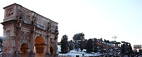 Rome, Fora: A peculiar view of the Arc of Costantino (in foreground, on the left) and of the Arc of Tito (on the background, on the right), in a snow-clad frame, with in particular the ancient ruins, the trees and the lawn among them covered by snow. The photo is taken in the late afternoon, after a snowing night (February, 2012).  This is an enlargement of a part of the original photo.