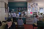 Man head in hands reading newspaper, bored. Regency Café  Westminster London SW1 UK.
