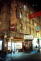The exterior of an old building in Chinatown with signs in English and Chinese dialects advertising a variety of products and a dot.com address. San Francisco, California.