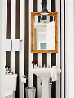 Monochrome stripes are broken by a bamboo mirror in this simple, yet dramatic black and white bathroom. The vertical lines give the appearance of extra height.