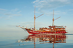 Misool, Raja Ampat, Indonesia; Boo area, a red, wooden sailing ship reflecting in the calm water's surface