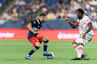 FOXBOROUGH, MA - JULY 7: Carles Gil #22 of New England Revolution dribbles as Ayo Akinola #20 of Toronto FC defends during a game between Toronto FC and New England Revolution at Gillette Stadium on July 7, 2021 in Foxborough, Massachusetts.