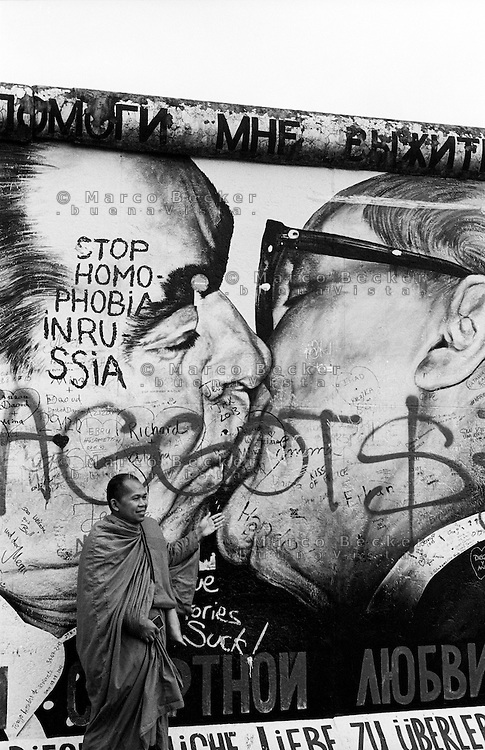 """Berlino, resti del Muro (East Side Gallery). Un monaco buddista posa davanti al celebre bacio """"alla sovietica"""" tra Leonid Il'ič Brežnev ed Erich Honecker. La scritta Stop omofobia in Russia --- Berlin, remains of the Wall (East Side Gallery). A buddhist monk posing in front of the famous socialist fraternal kiss between Leonid Brezhnev and Erich Honecker. The writing Stop omophobia in Russia"""