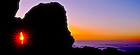 Sunrise peeks through a rock formation at 9,745 feet in Haleakala National Park, Maui.