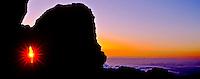 Sunrise peeks through a rock formation at 9,745 feet in Haleakala National Park, Maui.