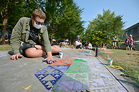 Otis Leimbach, a junior at Thaden School in Bentonville, stamps mathematical patterns Friday, Sept. 10, 2021, onto the sidewalk during the University of Arkansas Honors College Math Circus at Gearhart Hall on the university campus in Fayetteville. The event offered visitors a chance to build mathematical structures and to decorate with mathematical designs as a part of the larger celebration of the university's 150th birthday, Visit nwaonline.com/210911Daily/ for today's photo gallery.<br /> (NWA Democrat-Gazette/Andy Shupe)
