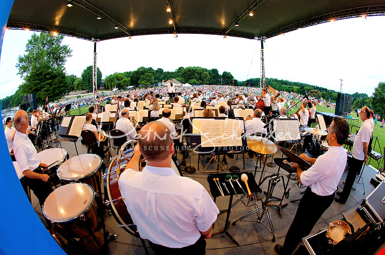 """Event photography of the Charlotte Symphony performing in a free outdoor concert June 17, 2012 at Duke Energy's McGuire Nuclear Station EnergyExplorium in Cornelius, NC. The symphony orchestra performed a """"musical travels"""" program. Jacomo Rafael Bairos conducted."""