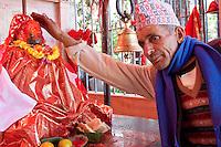 Kathmandu, Nepal.  Hindu Priest in front of Statue to Hanuman, the Monkey God, in a Neighborhood Temple.