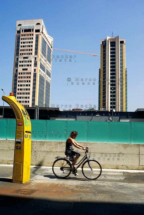 """Milano, quartiere Garibaldi, progetto di riqualificazione dell'area di Porta Nuova. Una donna in bicicletta, una colonnina per taxi e le Torri Garibaldi --- Milan, Garibaldi district,  requalification project of """"Porta Nuova"""" area. A woman on a bicycle, a taxi column and the skyscrapers """"Torri Garibaldi"""""""