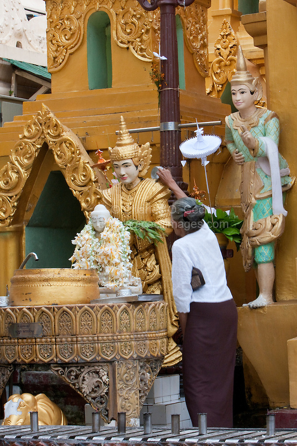 Myanmar, Burma.  Shwedagon Pagoda, Yangon, Rangoon.  Worshiper pours purifying water over protective deity, a nat, one of many Buddhist spirits worshipped in Myanmar.