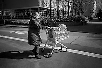 "Switzerland. Canton Ticino. Lugano. An elderly woman wears a mask on the face to protect herself from the Coronavirus (also called Covid-19). She pushes a supermarket trolley fully loaded with plastic bottles of water. She bought them in order to stock water bottles at home. Swiss Alpina mineral water rises up through the Valais Alps. Deep inside the mountains, the water is naturally purified and enriched with minerals, which gives this absolutely natural product its unique flavour. Swiss Alpina is a mineral water from the heart of the Swiss Alps.. Due to the spread of the coronavirus, the Federal Council has categorised the situation in the country as ""extraordinary"". It has issued a recommendation to all citizens to stay at home, especially the sick and the elderly. The Federal Council (German: Bundesrat, French: Conseil fédéral, Italian: Consiglio federale, Romansh: Cussegl federal) is the seven-member executive council that constitutes the federal government of the Swiss Confederation. Coop is one of Switzerland's largest retail and wholesale companies. It is structured in the form of a cooperative society with around 2.5 million members. 24.03.2020 © 2020 Didier Ruef"