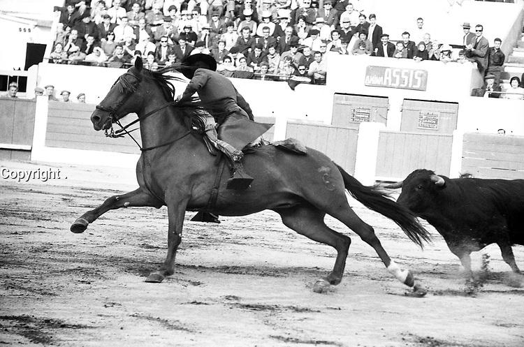 Corrida aux Arènes du Soleil d'Or (quartier des Arènes). 2 octobre 1966. Scène de tauromachie à cheval (rejoneo). Au 1er plan la caballera Amina Assis sur son cheval est poursuivie par le taureau