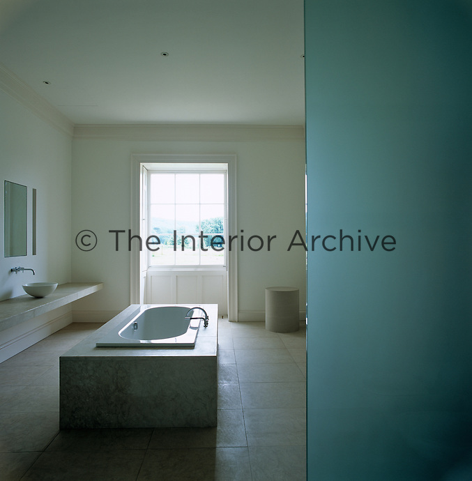 A white marble bath on a limestone floor is enclosed within panels of opaque blue glass